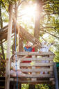 three cool kids with superheroes costumes playing on their homemade tree house, in the afternoon sun, lower austria, austria - HMEF00568