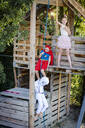 Three kids with superheroes costumes playing on their homemade tree house - HMEF00571