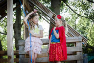Girls dressed up as princess and superwoman playing in a tree house - HMEF00574