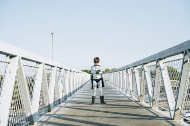 Portrait of boy disguised as superhero standing on a footbridge - JCMF00216