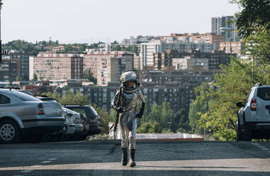 Boy dressed as an astronaut walking on a street in the city - JCMF00219