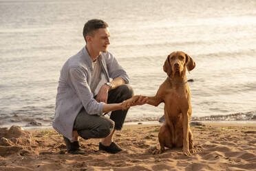 young man with his dog at the beach, dog giving paw - VPIF01524
