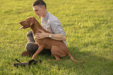 young man with his dog, cuddling on a meadow - VPIF01530