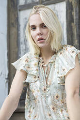 Portrait of blond young woman wearing summer blouse with floral design - JESF00319
