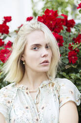Portrait of blond young woman wearing summer blouse with floral design - JESF00322