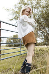 Portrait of blond young woman wearing white blouse, mini skirt and Wellington Boots - JESF00325
