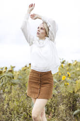 Portrait of blond young woman wearing white blouse dancing on sunflower field - JESF00328