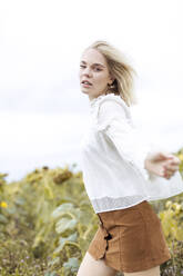 Portrait of blond young woman wearing white blouse dancing on sunflower field - JESF00331