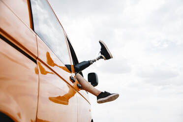 Legs of prosthetic young man dangling out of camper van window - CJMF00010