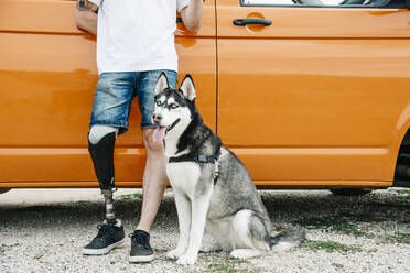 Young man with dog wearing leg prosthesis at camper van - CJMF00016