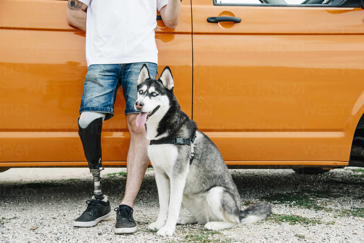Young man with dog wearing leg prosthesis at camper van - CJMF00016 - Jesús Martinez/Westend61