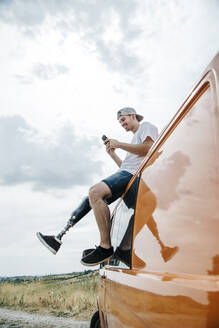 Young man with leg prosthesis sitting on roof of camper van using cell phone - CJMF00019