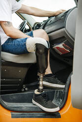 Young man with leg prosthesis sitting in camper van - CJMF00025