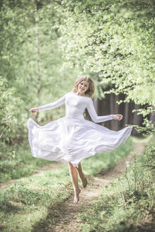 Young woman wearing white dress, dancing in the forest - STBF00389