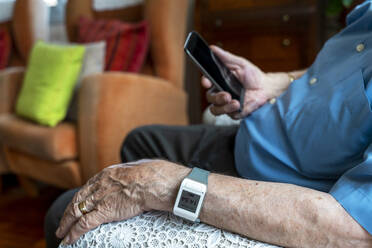 Elderly man using a mobile phone and wearing a smart emergency alarm bracelet around wrist at home - GEMF03151