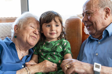 Grandparents spending time with the granddaughter in living room - GEMF03157