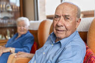 Elderly man with his wife sitting in an armchair in living room - GEMF03160