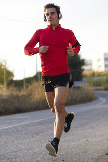 Portrait of sporty young man running in the street. LLeida, catalonia, Spain - JSRF00579