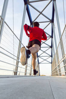 Jogger with smartphone in arm pocket running on a bridge - JSRF00588