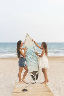 Two happy female friends with surfboard standing on boardwalk on the beach - DLTSF00120
