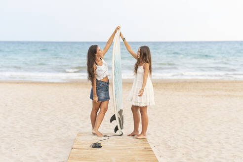 Two happy female friends with surfboard standing on boardwalk on the beach - DLTSF00123