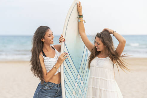 Two happy female friends with surfboard on the beach - DLTSF00126