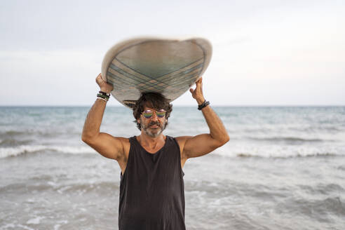 Portrait of mature man carrying surfboard at the sea - DLTSF00147