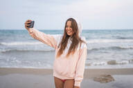 Happy young woman taking a selfie on the beach - DLTSF00150