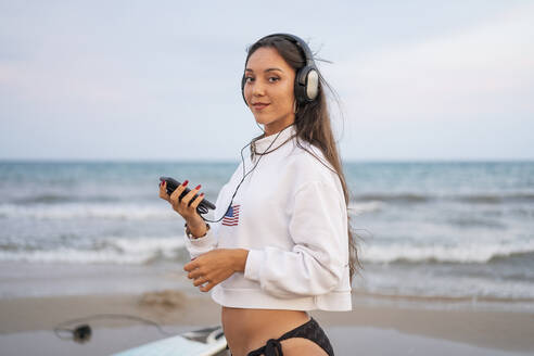 girl on the beach listening music with headphones/SPAIN/ALICANTE/ALICANTE - DLTSF00153