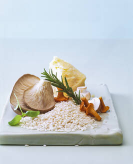 Close-up of raw ingredients for cooking Risotto on table against wall - PPXF00280