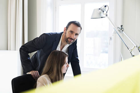Portrait of confident businessman with employee in office - MIKF00001