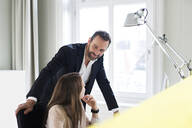 Businessman and employee talking at desk in office - MIKF00007