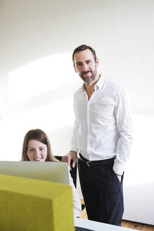 Portrait of confident businessman with employee in office - MIKF00010
