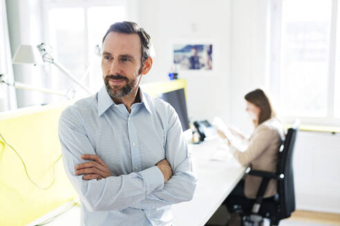 Portrait of confident businessman in office with employee in background - MIKF00016