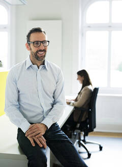 Happy businessman in office with employee in background - MIKF00019