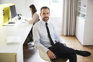 Portrait of confident businessman in office with employee in background - MIKF00025