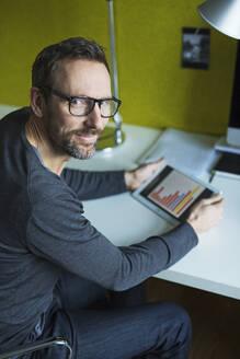 Portrait of confident businessman using tablet at desk in office - MIK00055