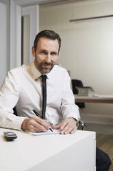 Portrait of confident businessman sitting at desk in office taking notes - MIK00058