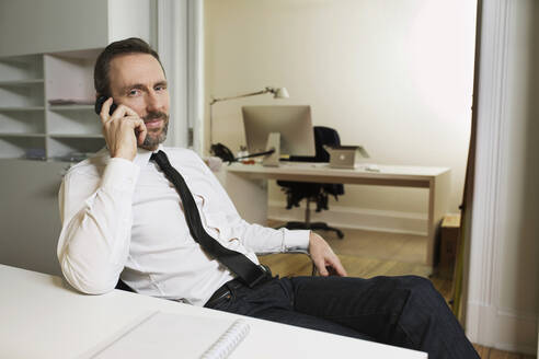Businessman talking on the phone at desk in office - MIK00061