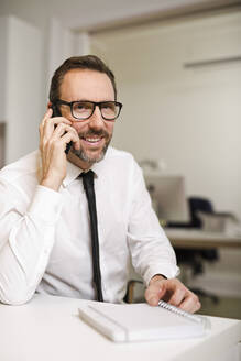 Businessman talking on the phone at desk in office - MIK00064