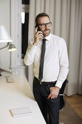 Smiling businessman talking on the phone in office - MIK00067