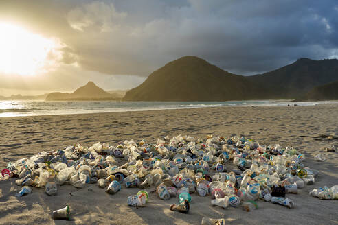 Pile of plastic rubbish dumped on the sand at sunset on Selong Belanak Beach on Lombok, Indonesia, Southeast Asia, Asia - RHPLF11953