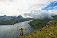 Man with open arms rejoices looking to the fjords, Funningur, Eysturoy island, Faroe Islands, Denmark, Europe - RHPLF12100