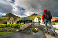 Hiker in the traditional village of Gjogv, Eysturoy island, Faroe Islands, Denmark, Europe - RHPLF12121
