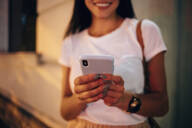 Young woman using smartphone in the city at night - OYF00063