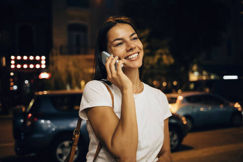 Young woman using smartphone in the city at night - OYF00066