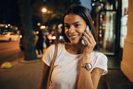 Young woman using smartphone in the city at night - OYF00069
