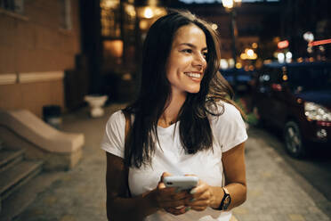 Young woman using smartphone in the city at night - OYF00072