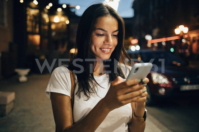 Young woman using smartphone in the city at night - OYF00075 - alev/Westend61