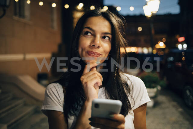 Young woman using smartphone in the city at night, looking up - OYF00078 - alev/Westend61
